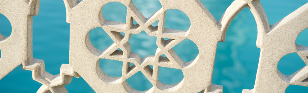 Islamic star pattern architectural detail on fence in front of bright blue water background